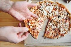Eine Leute, die Scheiben der Pizza aus dem Kasten heraus nehmen schnelle Lieferung des Lebensmittels Verpackung für Schnellimbiß  Lizenzfreies Stockbild