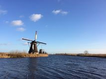 Eine Linie von Windmühlen durch das Kinderdijk nahe Rotterdam, die Niederlande stockfotografie