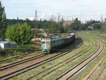 Eine Lokomotive, die einige Autos im Industriegebiet zieht Lizenzfreie Stockfotos