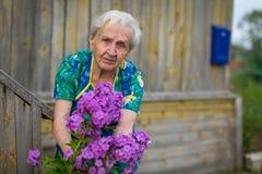Eine ältere Frau beschäftigt mit den Blumen Stockfotografie