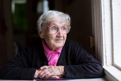 Eine ältere Frau, die nahe dem Fenster sitzt Porträt Stockbilder