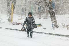 Eine ?ltere Frau geht in den Schnee auf dem B?rgersteig und lehnt sich auf einem Stock lizenzfreie stockfotografie
