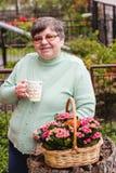 Eine ältere Frau mit einer Tasse Tee wünscht einen schönen Tag Stockbild