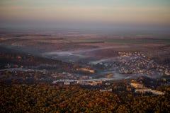 Eine Luftaufnahme eines Dorfs nahe einem Wald, auf den der Nebel fällt Stockfoto