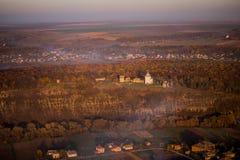 Eine Luftaufnahme eines Dorfs nahe einem Wald, auf den der Nebel fällt Lizenzfreies Stockbild