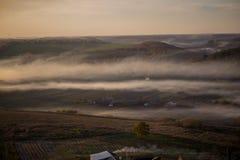 Eine Luftaufnahme eines Dorfs nahe einem Wald, auf den der Nebel fällt Lizenzfreie Stockbilder