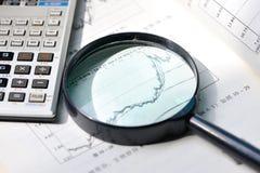 Eine Lupe, die auf Aktienkurve sich konzentriert stockbild