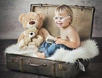 Eine lustige Abbildung des kleinen Jungen im Koffer Stockfotografie