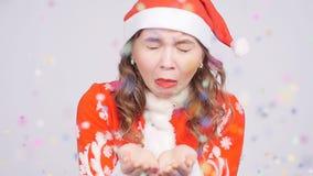 Eine lustige junge Frau in Santa Claus-Hut niest an den Konfettis stock video footage