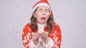 Eine lustige junge Frau in Santa Claus-Hut niest an den Konfettis stock video