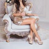 Eine luxuriöse Frau sitzt in einem teuren Stuhl gegen das backdro lizenzfreie stockfotografie