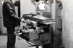 Eine männliche Arbeitskraft arbeitet an einer größeren Metalleisen-Bauschlosserdrehbank, Ausrüstung für Reparaturen, Metallarbeit stockbilder