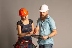Eine männliche Architekten- oder Ingenieursitzung mit einem Gebäudefrauenauftragnehmer auf grauem Hintergrund stockfotografie