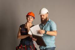 Eine männliche Architekten- oder Ingenieursitzung mit einem Gebäudefrauenauftragnehmer auf grauem Hintergrund stockfotos
