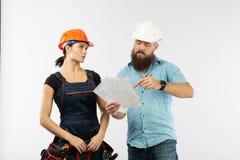 Eine männliche Architekten- oder Ingenieursitzung mit einem Gebäudefrauenauftragnehmer auf weißem Hintergrund lizenzfreie stockfotografie