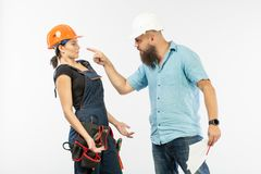 Eine männliche Architekten- oder Ingenieursitzung mit einem Gebäudefrauenauftragnehmer auf weißem Hintergrund lizenzfreie stockbilder
