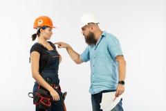 Eine männliche Architekten- oder Ingenieursitzung mit einem Gebäudefrauenauftragnehmer auf weißem Hintergrund stockfotografie