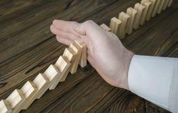 Eine männliche Hand, die den Domino-Effekt stoppt lizenzfreies stockfoto