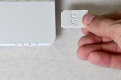 Eine männliche Hand fügt eine weiße Karte des Vertrages Sd in den entsprechenden Input in der Seite des weißen netbook ein Mann v stockfotografie