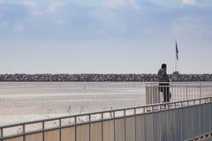 Eine männliche schauende USA-Flagge auf Ozeanbruchwand Lizenzfreie Stockfotos