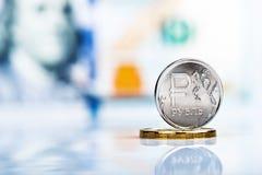Eine Münze des russischen Rubels gegen 100 US-Dollar Banknote Lizenzfreie Stockfotos