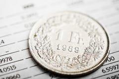 Eine Münze des Schweizer Franken auf schwankendem Diagramm Stockbild