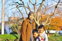 Eine malaysische Familie, die für die Kamera im Herbst aufwirft Stockfotografie