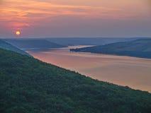 Eine malerische Ansicht der Flussbucht mitten in den grünen Bergen gegen den Abendsonnenuntergang Stockbilder