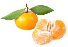 Eine Mandarine mit Grünblättern und -segmenten Stockfoto