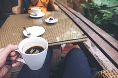 Eine Mann ` s Hand, die eine schwarze Kaffeetasse und eine Frau im Hintergrund im Café hält Stockfotografie