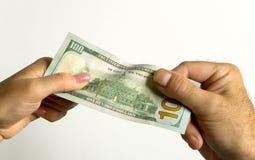Eine Mann ` s Hand und eine Frau ` s Hand halten eine Hundertdollar-Rechnung Lizenzfreie Stockfotos