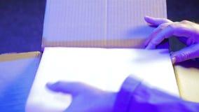 Eine Mannbelichtungseinheit verlässt einen Kasten ein neues Rohr für einen Profilscheinwerfer stock video