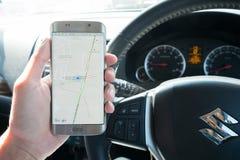Eine Mannhand, die das Bildschirmfoto von Google-Karte darstellend auf Rand Samsungs-Galaxie s6 hält Lizenzfreie Stockfotos