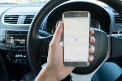 Eine Mannhand, die das Bildschirmfoto von Google-Karte darstellend auf Rand Samsungs-Galaxie s6 hält Stockfotografie