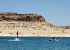Eine Mannstellung auf Wasserstrahlen an einem Reservoir in der Wüste lizenzfreies stockbild