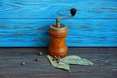 Eine mechanische Mühle und ein Pfeffer mit einem Lorbeer treiben auf einem Holztisch Blätter lizenzfreies stockfoto