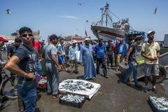 Eine Menge tritt entlang dem Dock des Fischereihafens in Essaouira in Marokko zusammen Lizenzfreie Stockbilder