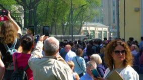 Eine Menge von den Leuten, welche die Parade der militärischer Ausrüstung zu gehen, Behälter aufpassen und Video an den Telefonen stock video footage