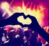 Eine Menge von Leuten an einem Konzert mit dem geformten Herzen überreicht Stockfotos