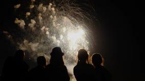 Eine Menge von Leuten passen bunte Feuerwerke auf und feiern stock footage