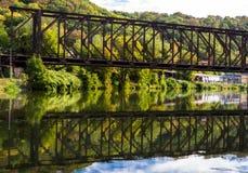 Eine Metalleisenbahnbrücke über einem Bett im Wald im Hintergrund von Bäumen in den Herbstfarben stockfotografie