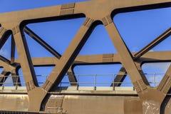Eine Metalleisenbahnbrücke mit einem klaren blauen Himmel durch die Strahlen stockbilder