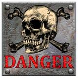 Eine Metallplatte mit einem Schädel und der Wortgefahr Stockbilder
