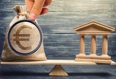 Eine Miniaturbank und ein Geld auf den Skalen Das Konzept der erfolgreichen Investition in der Bank Kredit/Darlehen/Ablagerung Da lizenzfreies stockfoto