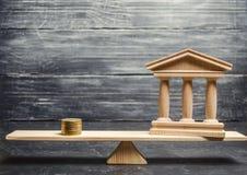 Eine Miniaturbank und ein Geld auf den Skalen Das Konzept der erfolgreichen Investition in der Bank Kredit/Darlehen/Ablagerung Da stockfoto