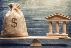 Eine Miniaturbank und ein Geld auf den Skalen Das Konzept der erfolgreichen Investition in der Bank Kredit/Darlehen/Ablagerung Da lizenzfreie stockfotografie