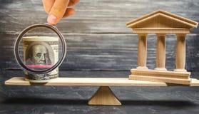Eine Miniaturbank und ein Geld auf den Skalen Das Konzept der erfolgreichen Investition in der Bank Kredit/Darlehen/Ablagerung Da lizenzfreies stockbild