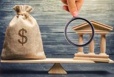 Eine Miniaturbank und ein Geld auf den Skalen Das Konzept der erfolgreichen Investition in der Bank Kredit/Darlehen/Ablagerung Da lizenzfreie stockbilder