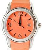 Eine Minute zu zwölf Uhr auf orange Armbanduhr Lizenzfreie Stockbilder