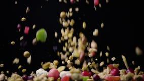 Eine Mischung von Trockenfrüchten und von Nüssen mit muesli fällt auf dem Tisch Zeitlupe stock footage